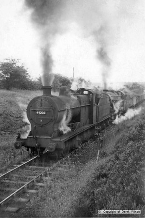 A Stanier 8F 2-8-0 piloted by  4F 0-6-0 no. 44202 are seen struggling up the gradient as they leave Clipstone colliery on the former Midland Railway single track.with a rake of loaded coal wagons. These would both be Kirkby-in-Ashfield (16B) loco's.  circa 1960