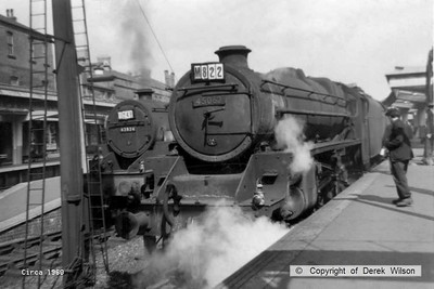 Stanier Black five 4-6-0 no. 45062 & 'crab' 2-6-0 no. 42824 are seen waiting to depart from Derby with summer Saturday seaside specials, circa 1960.