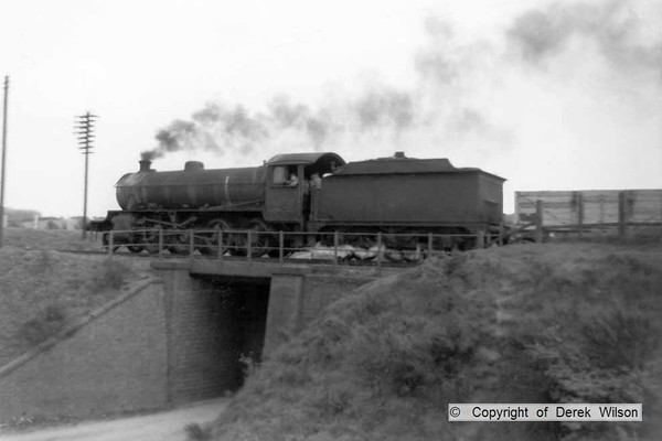 A unidentified LNER O1 2-8-0 is seen approaching Clipstone East signal box with a rake of coal wagons.  circa 1960