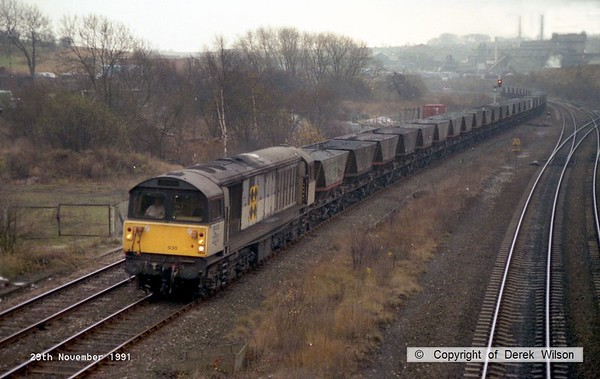 911129-001     Trainload Coal class 58 no 58030 passes through Clay Cross with a rake of empty coal hoppers.