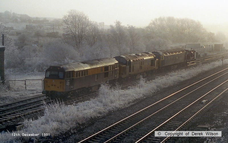 911212-006     Civil Engineers 'Dutch' livery class 31 no 31185 leads class 37 no 37716, class 47 no 47307, and a single brake van.  Captured on the down freight line, passing through the hoar frost at Clay Cross.