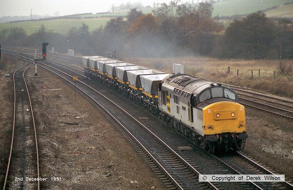 911202-003     Trainload Coal class 37 no 37239 is seen heading through Clay Cross on the up main with seven new coal hoppers in tow.