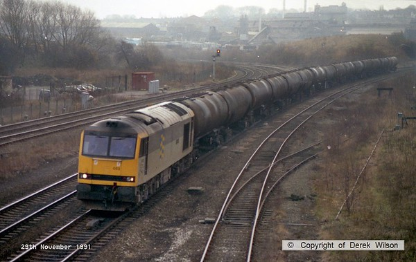 911129-002     Brush class 60 no 60053 John Reith heads north on the main at Clay Cross, hauling a rake of fuel-oil tanks.