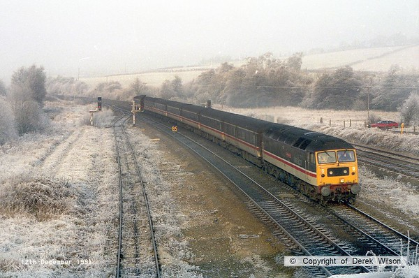 911212-004     A wintry scene at Clay Cross, with Intercity Cross Country class 47/8 no 47824 Glorious Devon, seen on the up main with a southbound service.